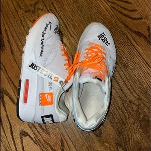 Nike sneakers that are orange, white, and black.